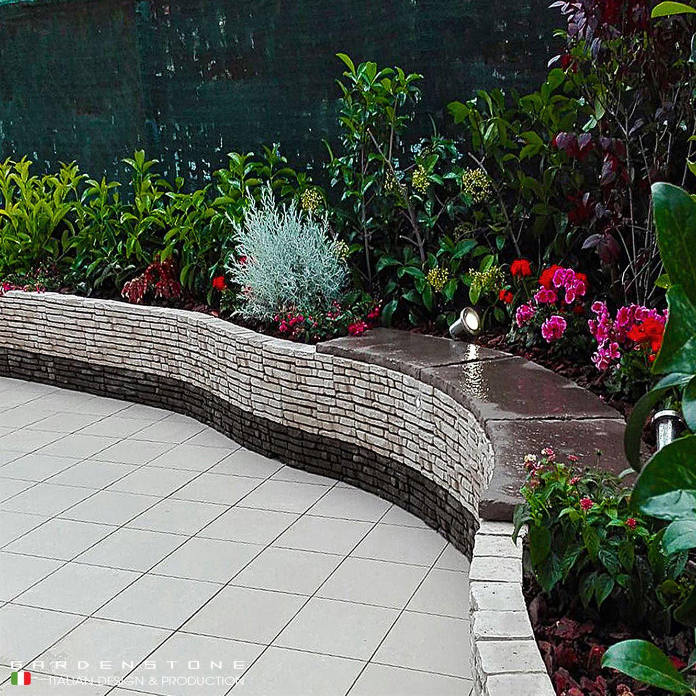 Muretto bicolore in finta pietra con posto per sedersi e circondato da piante