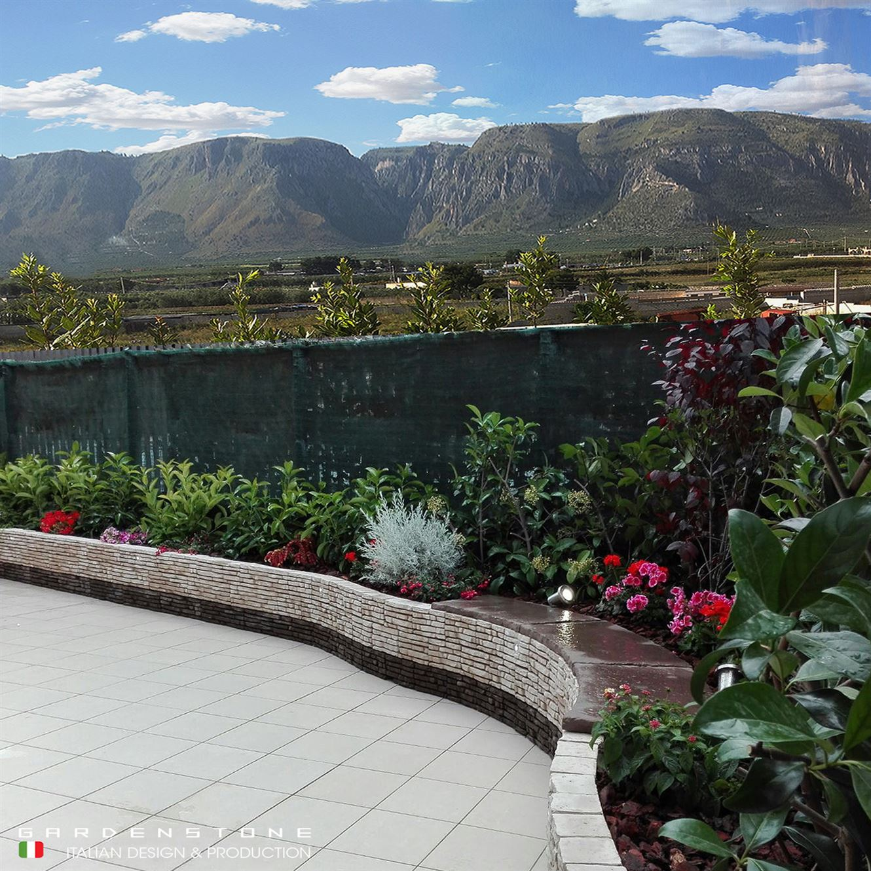 Muretto bicolore in finta pietra con posto per sedersi e piante