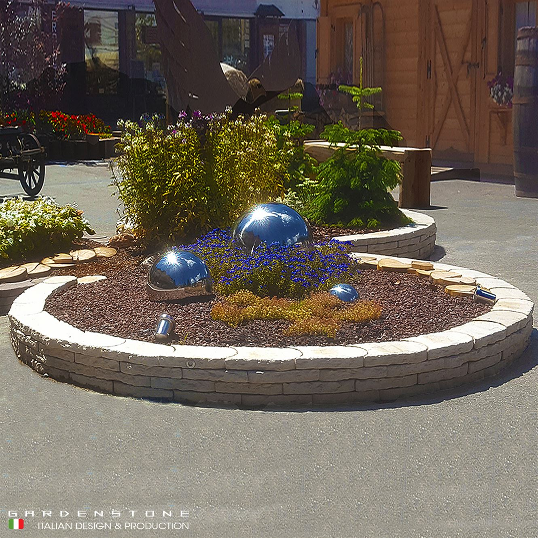 Muretto circolare per contenere aiuola con fiori e sfere decorative