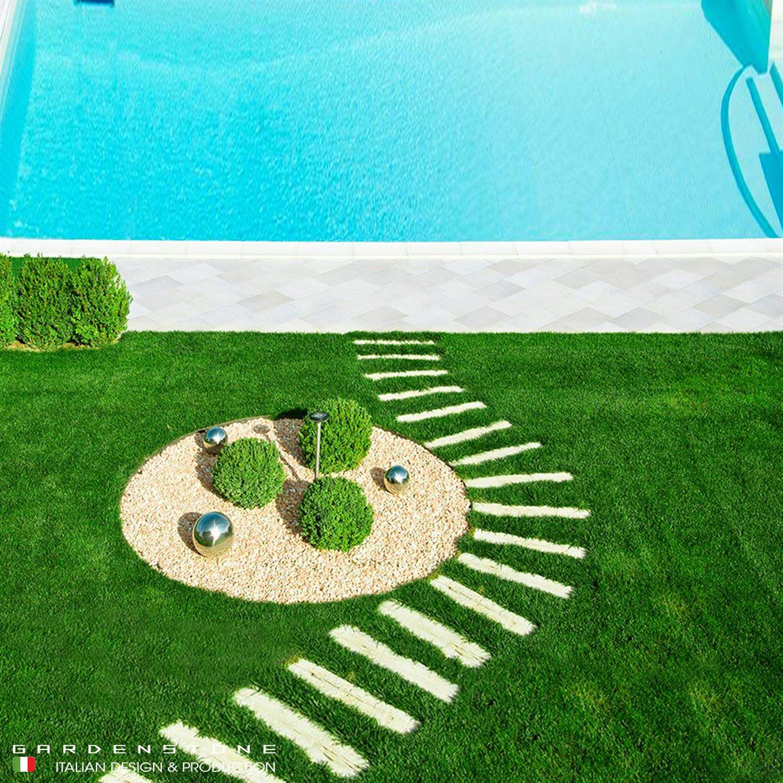 Camminamento irregolare di piastre in finta pietra distanziate che conducono alla piscina