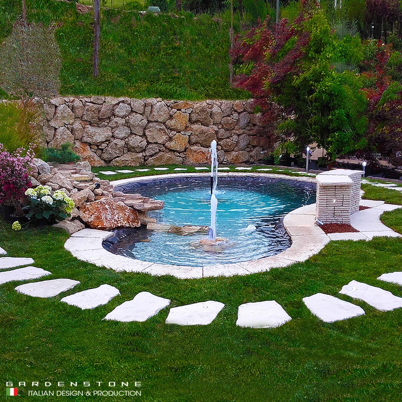 Camminamento di lastre irregolare e distanziate in finta pietra, che circondano il laghetto artificiale con cascata e muretto per sedersi