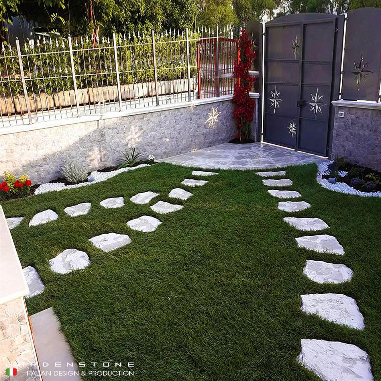 Camminamenti in finta pietra irregolari distanziati tra loro che conducono dal cancello all'entrata della casa, passando dal giardino
