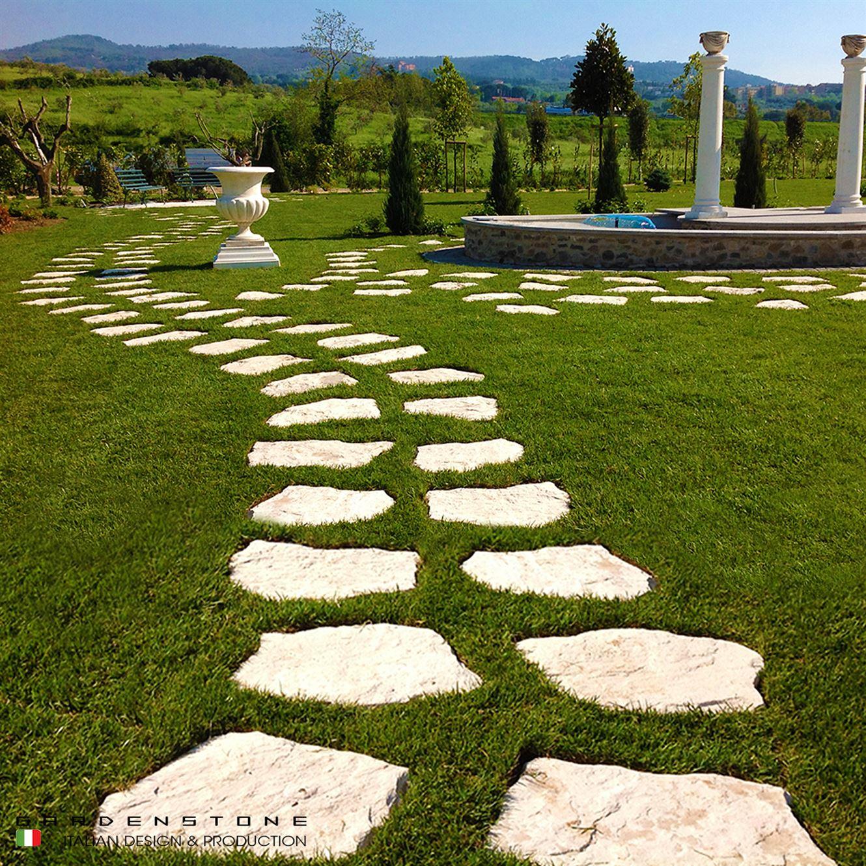 Camminamento con pavimentazione irregolare distanziati tra loro di sassi in finta pietra immerso nel verde