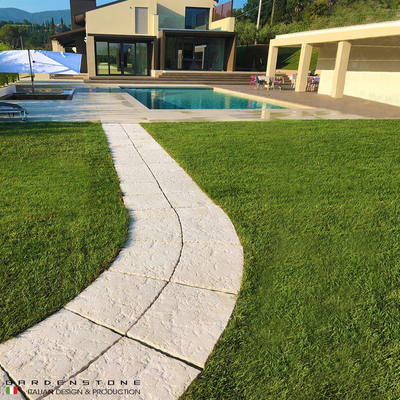 Camminamento a curva in finta pietra che conduce a piscina