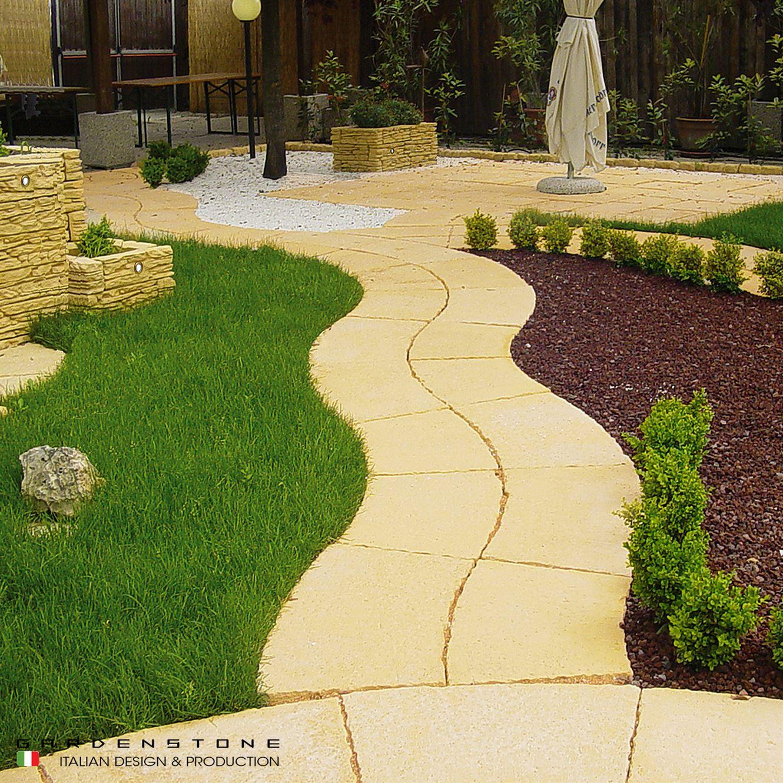 Camminamento da giardino immerso nel verde con muretti per aiuole in pietra ricostruita