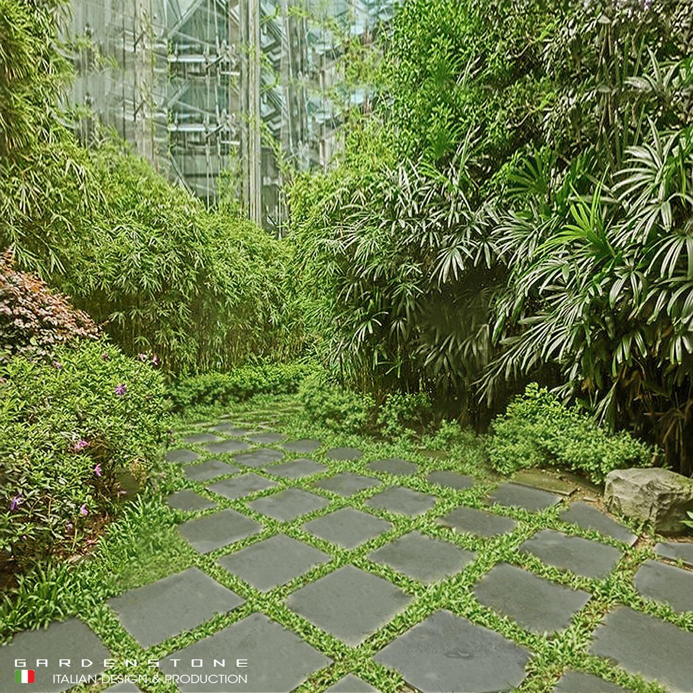 Pavimento con piastrelle regolari in finta pietra distanziate tra loro da fasci d'erba