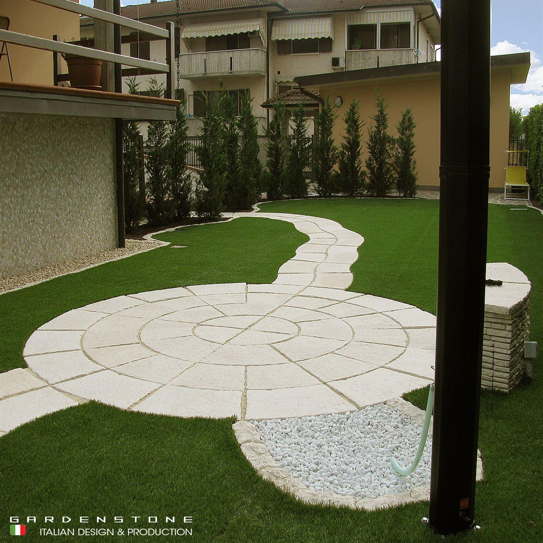 Pavimentazione circolare di piastrelle in finta con vialetto e muretto per sedersi