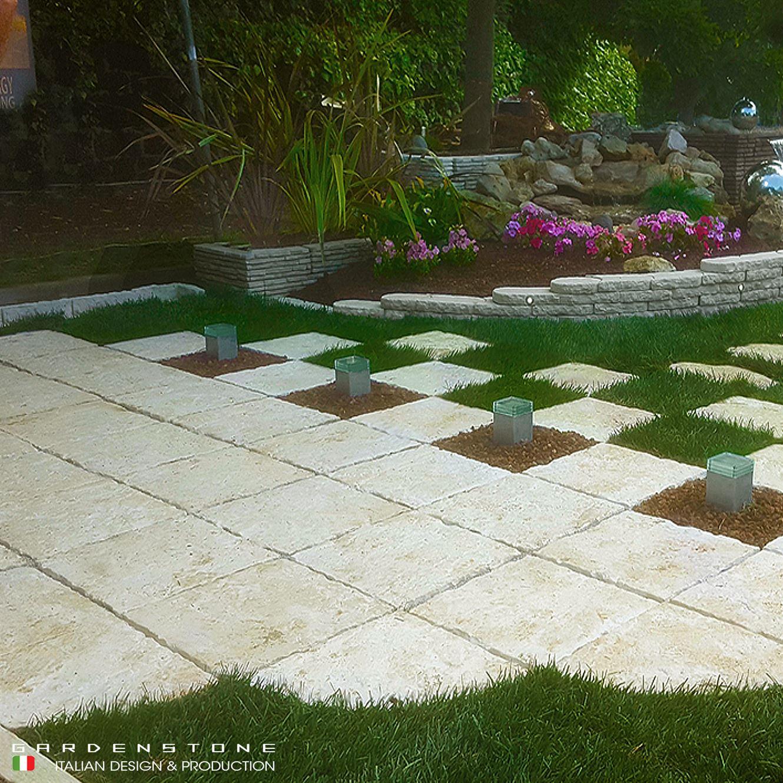 Pavimento con piastrelle con spazi per paletti luminosi su pavimento di sassi lavica