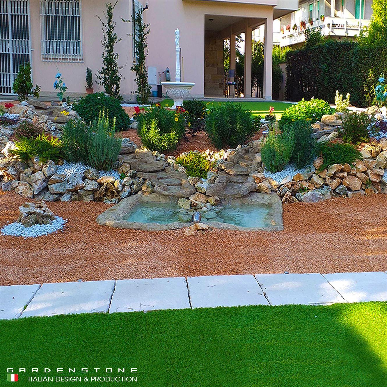Cascate da giardino artificiali immerse nel verde con camminamento in pietra dotato di faretti da incasso