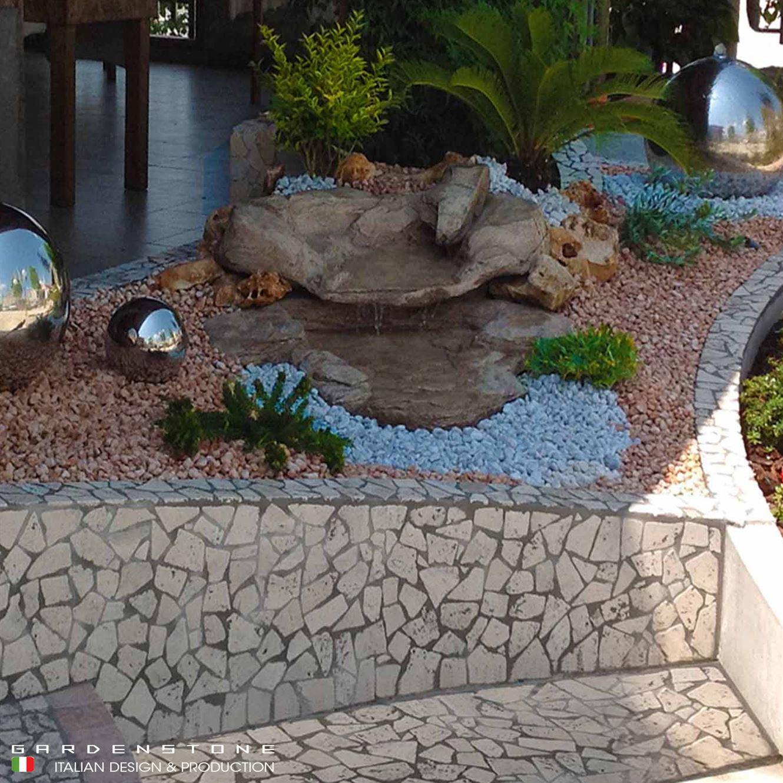 Cascata d'acqua decorativa sopra muretto con pavimentazione in sassi