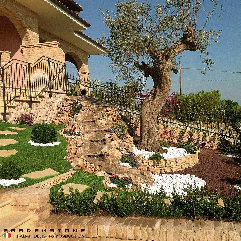 Cascata da giardino decorativa in finta pietra inserita in una aiuola