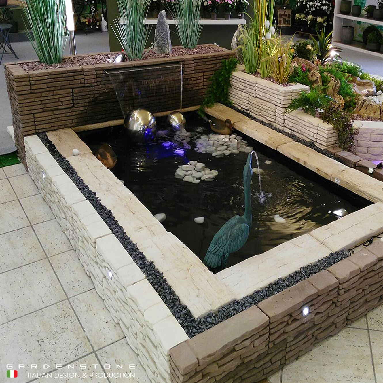 Lame d'acqua che sfociano in laghetto artificiale in finta pietra