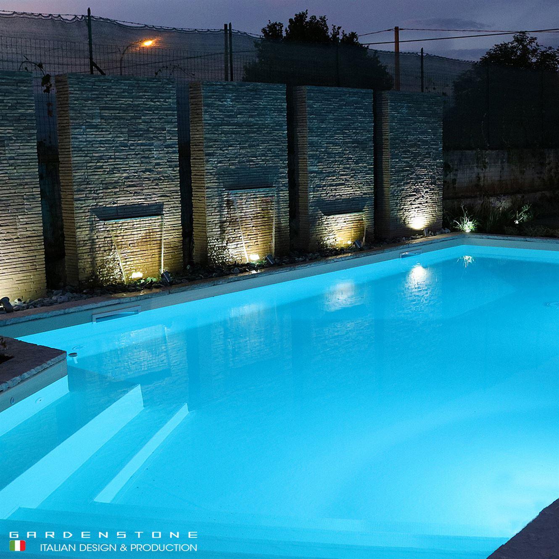 Lame d'acqua decorative a muro accanto a piscina in visione notturna