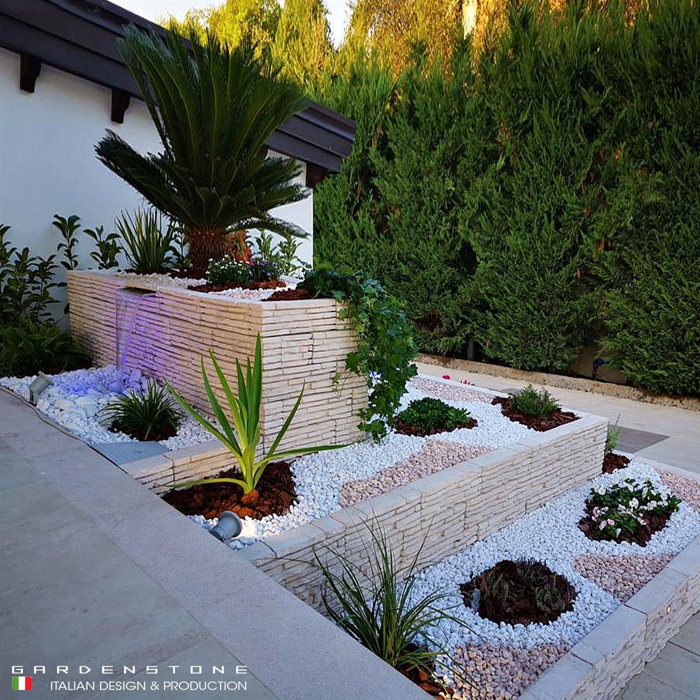 Muretti di diversa altezza e dimensione per contenere fiori e piante con pavimentazione in ciottoli