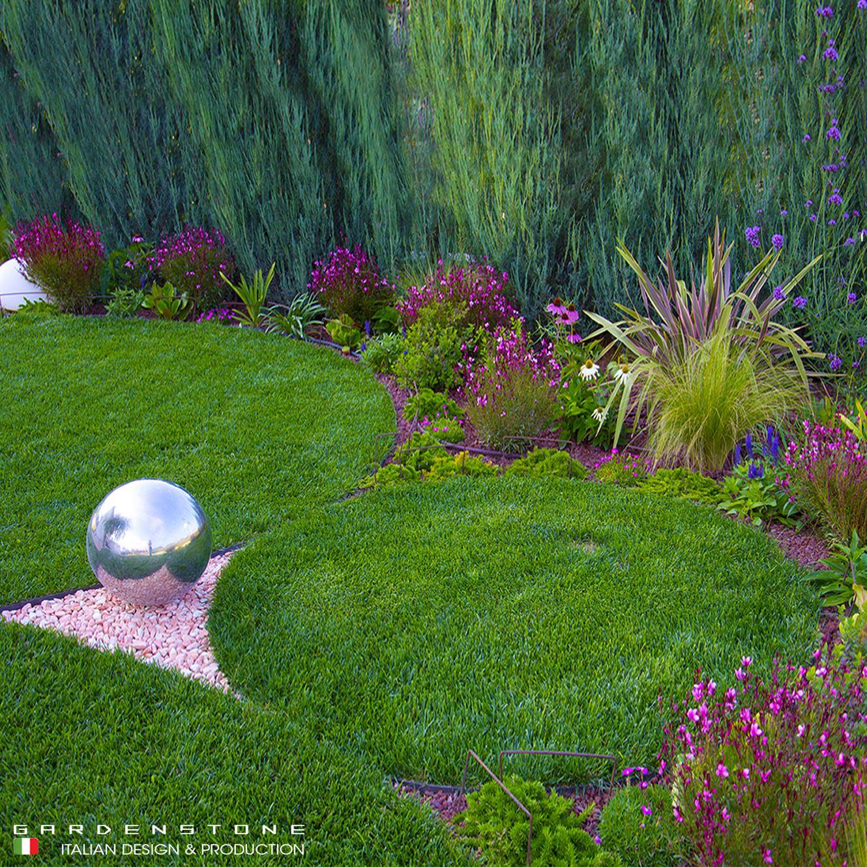 Sfera decorativa da giardino su pavimento in sassi rosa