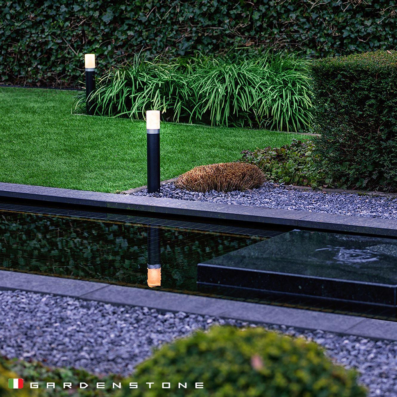 Lampioncini da giardino immersi nel verde e riflessi in un laghetto artificiale